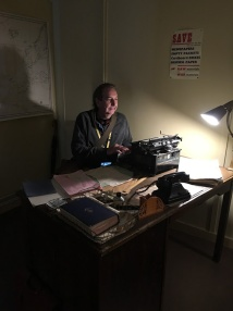 Bongo Man sitting at Alan Turing's desk